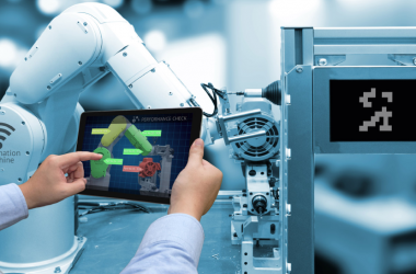 An image of a person operating industrial robot by using his tablet.